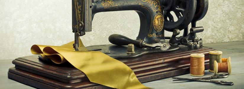 handbetriebene nähmaschine mit stoffen garnspulen und schere